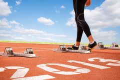 Track. Workout of athlete on start line of cinder-track with numerals of new year on sky background Stock Photos