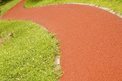 Track. A winding track by green grass Stock Photo