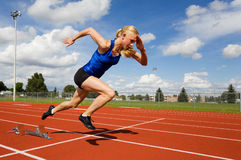 Track athlete. Exploding out of the starting blocks royalty free stock image