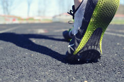 Track athlete image, of person walking on track before practice in the daylight.  Shows rubber under feet and hurdles in the back. Stock Images