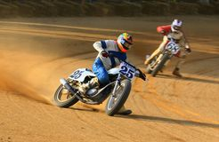 Track bike racing event. Dirt is kicked up in the air as the racing bike finishes the right hand turn Royalty Free Stock Photography