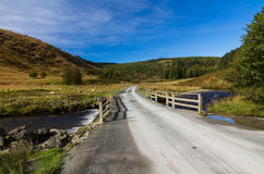 Track with bridge over river stream in mountain upland. Royalty Free Stock Images