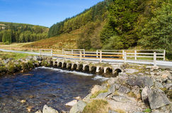 Track with bridge over river stream in mountain upland. Royalty Free Stock Photography