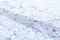 Track from a car tire on a gravel road after the first snowfall stock photography