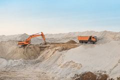 Track excavator loading soil on truck in front of a cloudy sky Stock Photos
