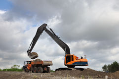 Loading a dumper truck. A Track excavator machine loading dumper truck with soil in front of a cloudy sky Stock Images