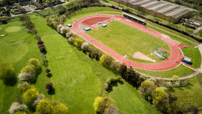 Track and field. Aerial photography of athletes training on a running track set by a golf course on a bright sunny day Stock Photography