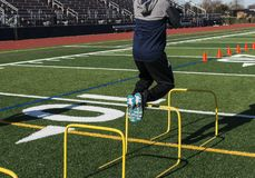 Jumping over hurdles for strength and coordination training. A track and field athlete jumping over yellow mini hurdles on a turf field from behind the runner Stock Photos