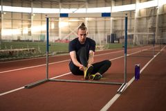 Track and field athlete tying his shoelaces before the training. The shot of track and field athlete tying his shoelaces before the training.Indoor training royalty free stock images