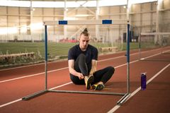 Track and field athlete tying his shoelaces before the training. The shot of track and field athlete tying his shoelaces before the training.Indoor training royalty free stock image