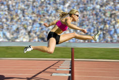 Track and Field Hurdler Athlete. Female track and field athlete hurdling stock photo