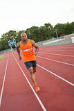 Track and Field Runner. African American man in his 30s running at a sports track outdoors Royalty Free Stock Photos