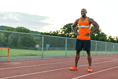 Track and Field Runner Smiling. African American man in his 30s posing at a sports track outdoors Royalty Free Stock Photos