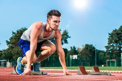 Track and field sprinter on starting point at cinder track in sp Stock Images
