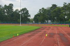 Track and fields with 2 yellow cone on track with artificial grass inside a stadium royalty free stock images