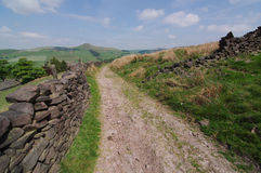 Track through hills bounded by dry-stone wall Stock Photos