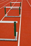 Track Hurdles. Three hurdles on a white stripped track Royalty Free Stock Images