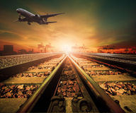 Track of railway and cargo plane flying above logistic ship port Royalty Free Stock Photos