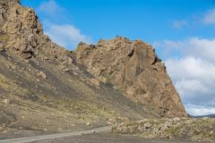 Track and rock hill through Iceland, blue sky Royalty Free Stock Image