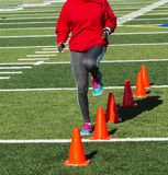 Track runner performing speed drill over orange cones Royalty Free Stock Photos