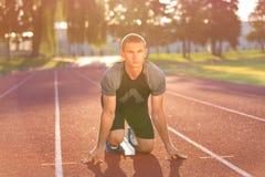Track runner in starting position on sunny morning. Stock Image