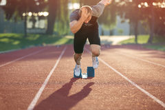 Track runner in starting position on sunny morning. Stock Photo
