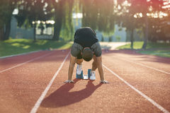 Track runner in starting position on sunny morning. Royalty Free Stock Photography