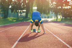 Track runner in starting position on sunny morning. Royalty Free Stock Images