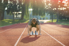 Track runner in starting position on sunny morning. Royalty Free Stock Photos