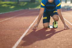 Track runner in starting position on sunny morning. Royalty Free Stock Image