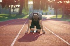 Track runner in starting position on sunny morning. Stock Photos