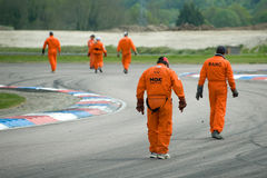 Track safety. THRUXTON, UNITED KINGDOM - MAY 1, 2011: Track safety marshalls inspect the circuit for debris between races at the British Touring Car Championship Royalty Free Stock Photography