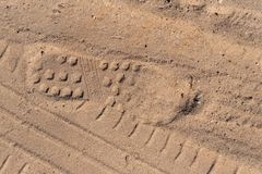 Track shoes and car wheels on sand stock image