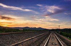 Track and sunset. Incomparable beauty of the sunset from the straight tracks next to fall down Stock Photo