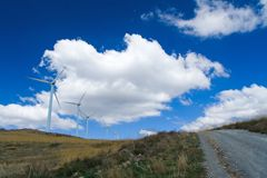 Track to the Windfarm. Wide angle view of a wind farm with large fluffy clouds. Polarizing filter gives strong blue and high contrast. This photo looks great in Stock Photos