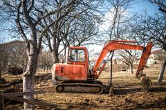 Track-type excavator loader, backhoe working on earth and loading at house construction site Stock Photo