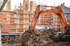 Track-type excavator loader working and loading at house construction site Royalty Free Stock Photo