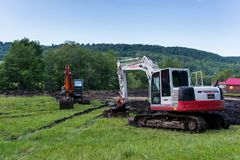 Tracked excavators near a small river , working on the creek bed. royalty free stock photography