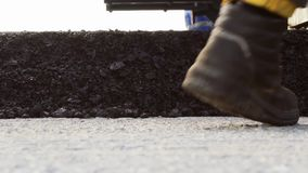 Tracked paver laying fresh asphalt pavement stock video
