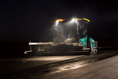 Tracked paver laying fresh asphalt pavement by night royalty free stock image