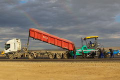 Tracked paver laying fresh asphalt pavement on a runway as part of the Danube Delta international airport expansion plan Stock Image