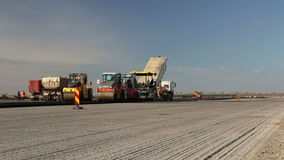 Tracked paver laying fresh asphalt pavement, time lapse stock footage