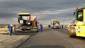 Tracked paver laying fresh asphalt pavement,time lapse stock video footage