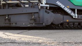 Tracked paver laying fresh asphalt pavement stock footage