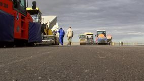 Tracked paver laying fresh asphalt pavement stock video footage