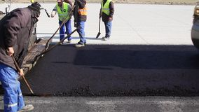 Tracked paver laying fresh asphalt pavement