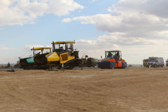 Tracked pavers laying fresh asphalt pavement on a runway as part of the Danube Delta international airport expansion plan Royalty Free Stock Photo