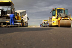Tracked pavers laying fresh asphalt pavement on a runway as part of the Danube Delta international airport expansion plan Stock Images