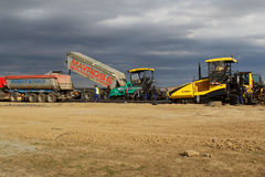 Tracked pavers laying fresh asphalt pavement on a runway as part of the Danube Delta international airport expansion plan Stock Image