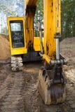 Trackhoe excavator. Older excavator hoe machine on muddy construction site with billowing diesel smoke exhaust stock photo